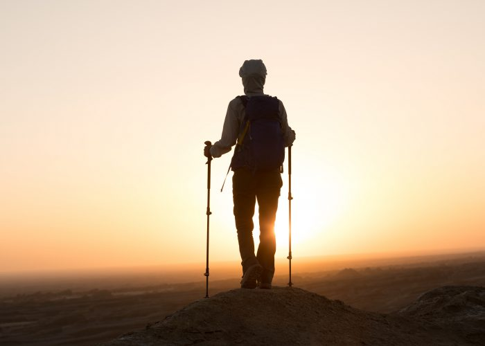 Successful woman hiker enjoy the view on sand desert in the sunset