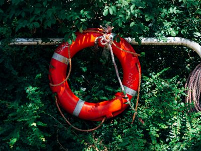 Red Lifebuoy Hanging on Grass Wall